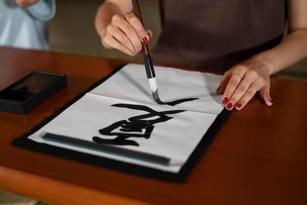 Primo piano su una persona che fa calligrafia giapponese, chiamata shodo