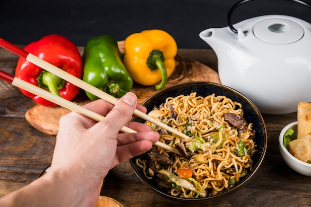 Close-up of a person eating the friend udon noodles with chopsticks