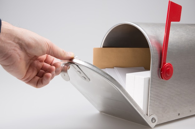 Close-up of a person hand checking mailbox in grey background