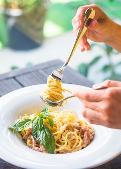 Close-up of a person holding appetizing spaghetti rolled on fork in the spoon