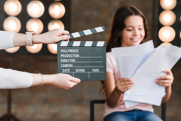 Close-up of a person holding clapper board in front of girl reading scripts