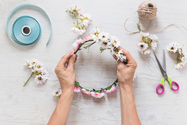 Close-up of a person holding fake floral wreath on textured backdrop