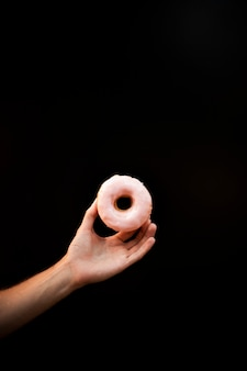 Close-up person holding glazed doughnut