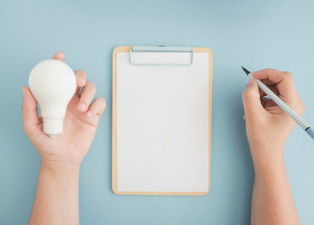 Close-up of a person holding light bulb writing with felt pen on clipboard