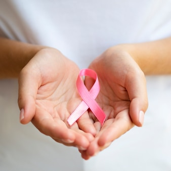 Close-up person holding pink ribbon