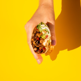 Close-up person holding tasty burrito