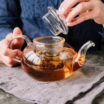 Крупным планом лицо с крышкой чайника