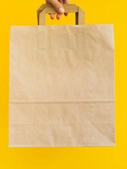 Крупным планом лицо, подняв бумажный мешок