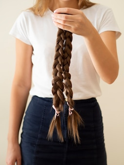 Close-up person holding up braids