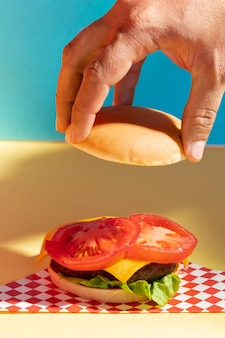 Close-up person holding up a burger bun