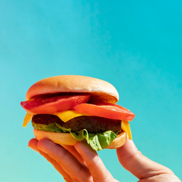 Close-up person holding up cheeseburger