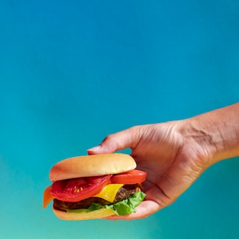 Close-up person holding up a cheeseburger