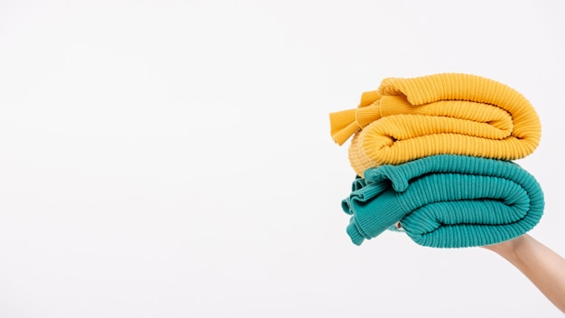 Close-up person holding up colourful sweaters
