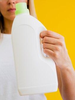 Крупный план лица, держащего бутылку с моющим средством