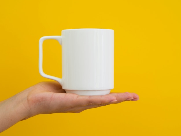 Close-up person holding up mug