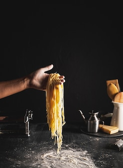 Close-up person holding up noodles