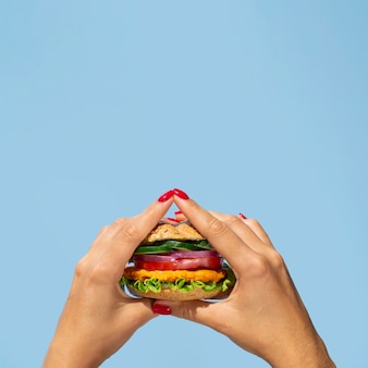 Close-up person holding a yummy veggie burger
