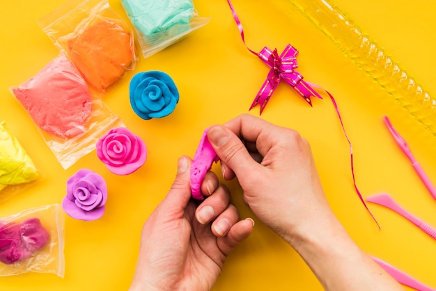 Close-up of a person making colorful clay rose on yellow backdrop