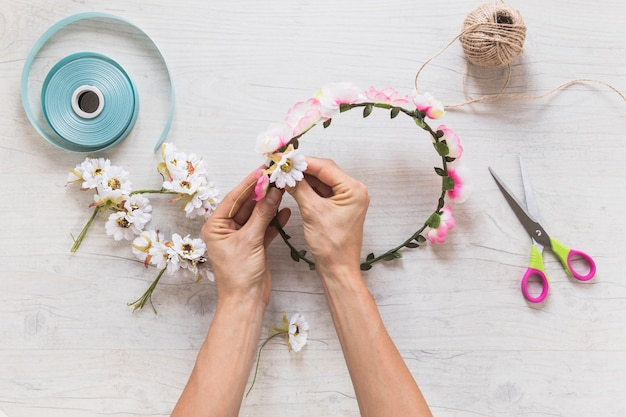 Close-up of a person making decorating flower wreath over white textured background