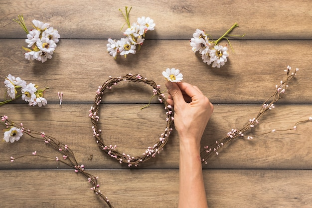 Close-up of person making flower and twig wreath on wooden table
