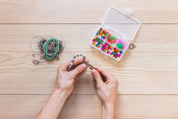 Close-up of a person making handmade bracelet with tweezers