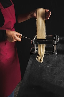 Close-up person making pasta with dark background