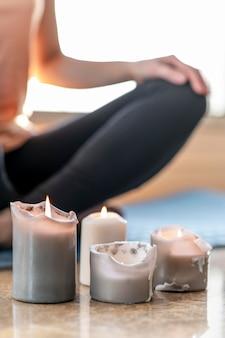 Крупным планом человек медитирует со свечами