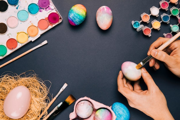 Close-up of a person painting the easter egg with brush on black background