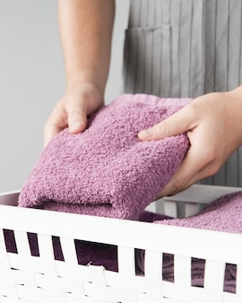 Close-up person placing towels in basket