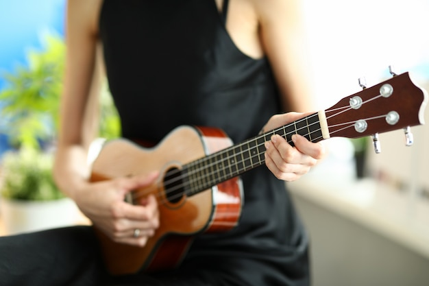 Close-up of person playing melody on ukulele. female elegant hand pressing on string. musical talent. simple black dress on artist. musical instrument and hobby concept