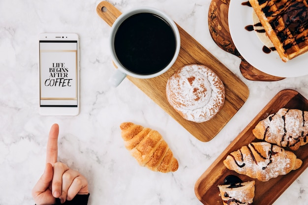 Close-up of a person pointing finger on cellphone with message and breakfast on marble textured backdrop
