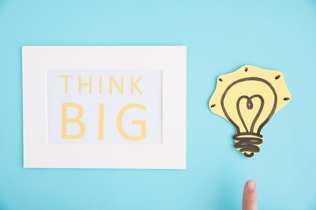 Close-up of a person pointing finger on light bulb near the think big white frame against blue background