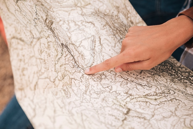 Close-up person pointing on a map