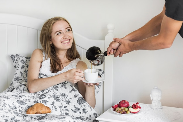 Close-up of a person pouring hot beverage in cup hold by a woman sitting on bed