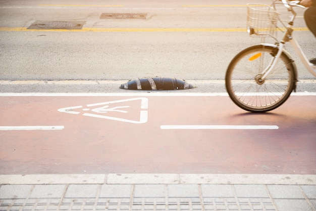 Close-up of a person riding the bicycle on road with warning triangle sign