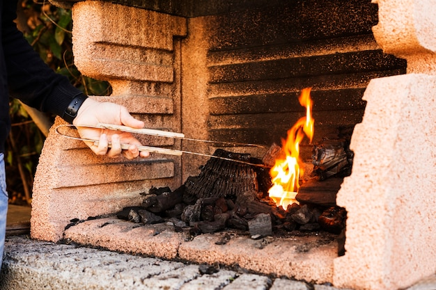 Close-up of a person's hand burning firepit