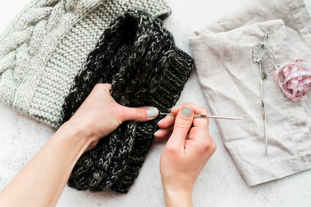 Close-up of a person's hand crocheting with wool
