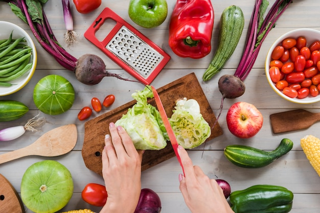 Close-up of a person's hand cutting cabbage with knife on chopping board surrounded with vegetables on table