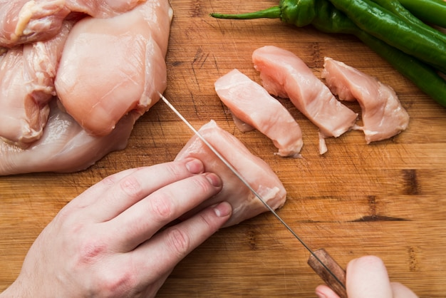 Close-up of a person's hand cutting raw chicken with knife on wooden table