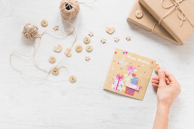 Close-up of a person's hand decorating birthday card on wooden backdrop