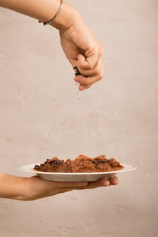 Close-up of a person's hand garnishing mexican beef dish