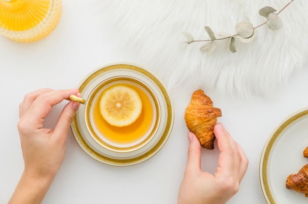 Close-up of a person's hand having croissant with lemon tea on white background