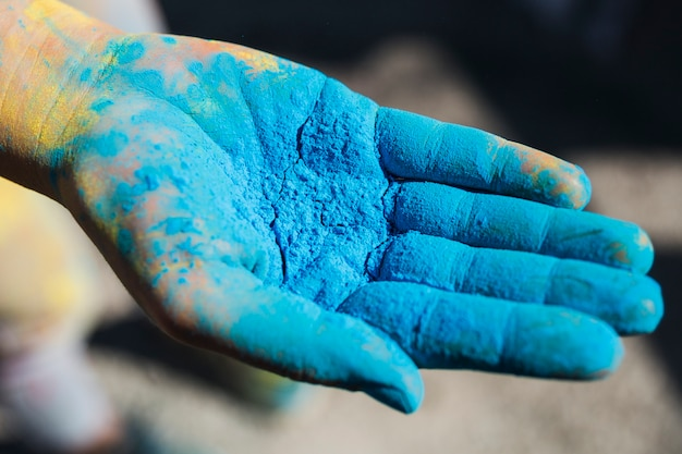 Close-up of a person's hand holding blue holi color