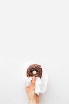 Close-up of a person's hand holding chocolate donut in tissue paper over white backdrop