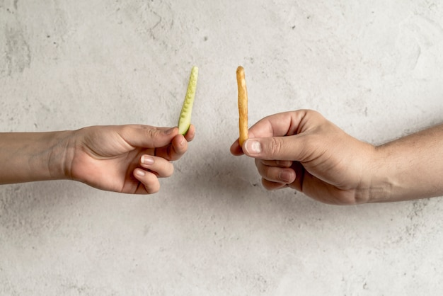 Close-up of person's hand holding cucumber slice and french fries over concrete background