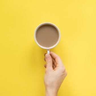 Close-up of a person's hand holding cup of coffee over yellow background