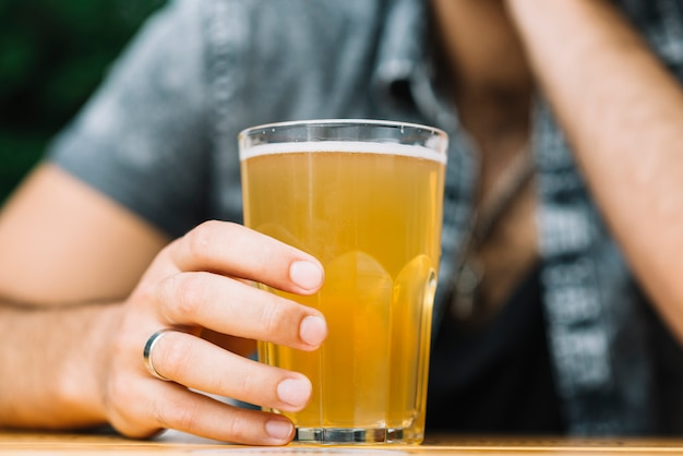 Close-up of a person's hand holding glass of beer