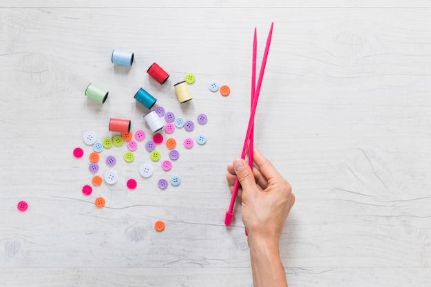 Primo piano della mano di una persona che tiene l'ago a maglia con rocchetto e bottoni sullo sfondo texture