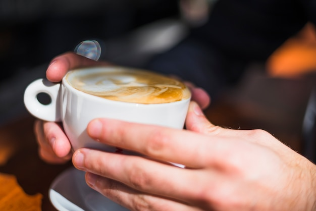 Close-up of a person's hand holding latte art coffee cup