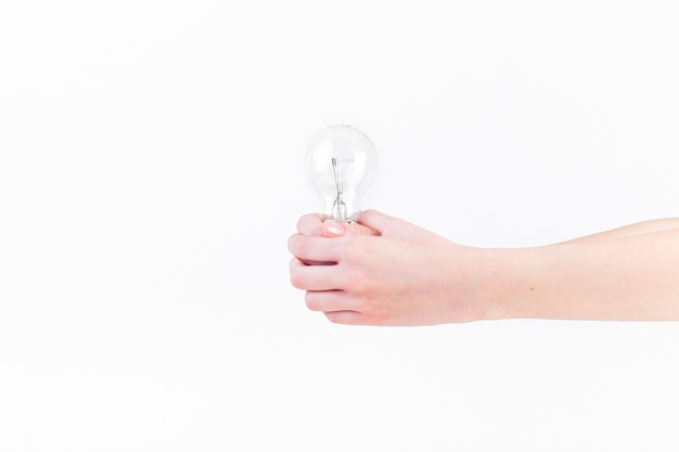 Close-up of a person's hand holding light bulb on white backdrop